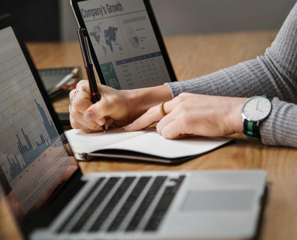 Női kéz ír egy füzetbe, miközben mindkét oldalán nagyon fontos grafikonokat mutató MacBook-ok vannak.