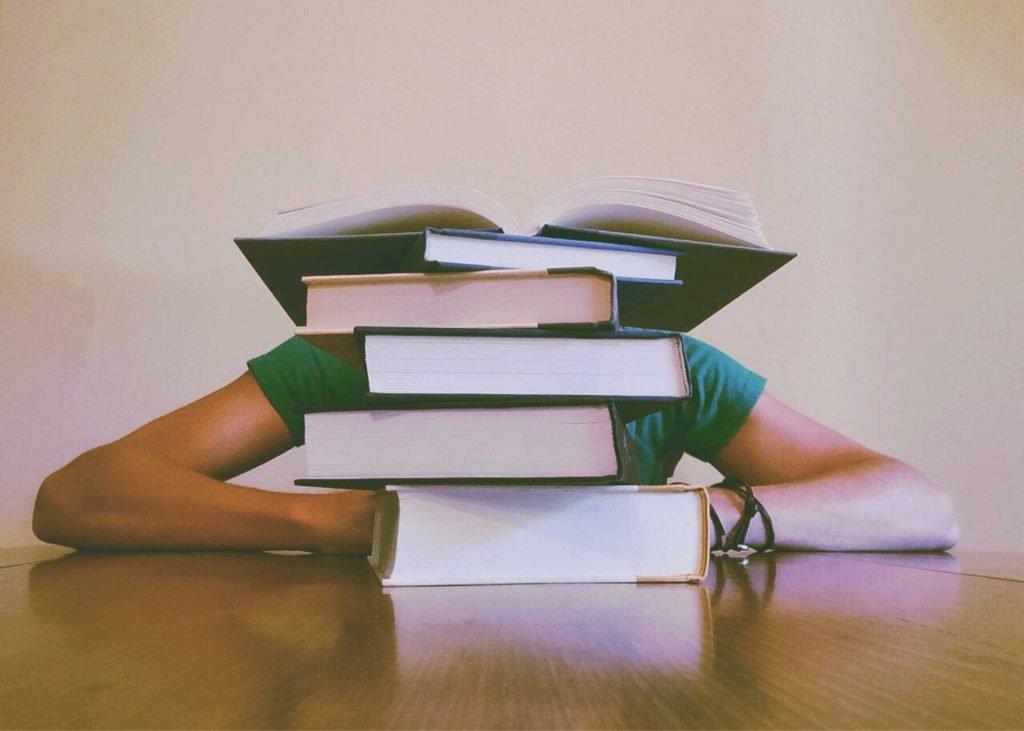 Sok könyv mögé borult lány