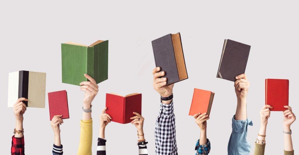 Kezek könyveket tartanak a magasba
